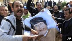 Masu zanga suna yiwa hoton Moammar Gadhafi fenti.