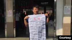 從中國大陸到台灣申請政治庇護的張文手持乞討說明。(溫起鋒提供)