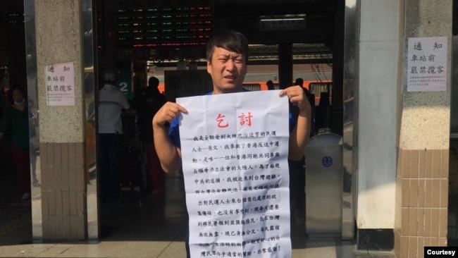 从中国大陆到台湾申请政治庇护的张文手持乞讨说明。(温起锋提供)