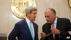 U.S. Secretary of State John Kerry and Egypt's Foreign Minister Sameh Shukri talk at the presidential palace in Cairo July 22, 2014.