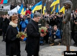 Ukraine's President Petro Poroshenko and wife Maryna place flowers at a monument for Holodomor victims, in Kyiv, Nov. 22, 2014. Millions died of starvationin the famine of 1932-33.