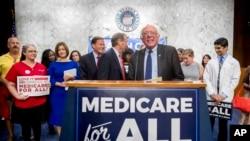 """资料照:无党派的桑德斯参议员和一些民主党参议员以及支持者抵达在国会山举行的记者会,倡导""""全民联邦医保""""。(2017年9月13日)"""