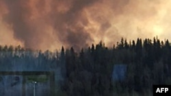 Smoke rises from a heavily wooded area in Fort McMurray, Alberta, May 3, 2016. Most residents were ordered to leave town after a wildfire swept through the oil sands region of Alberta. (Credit: Alberta Agriculture and Forestry Department)