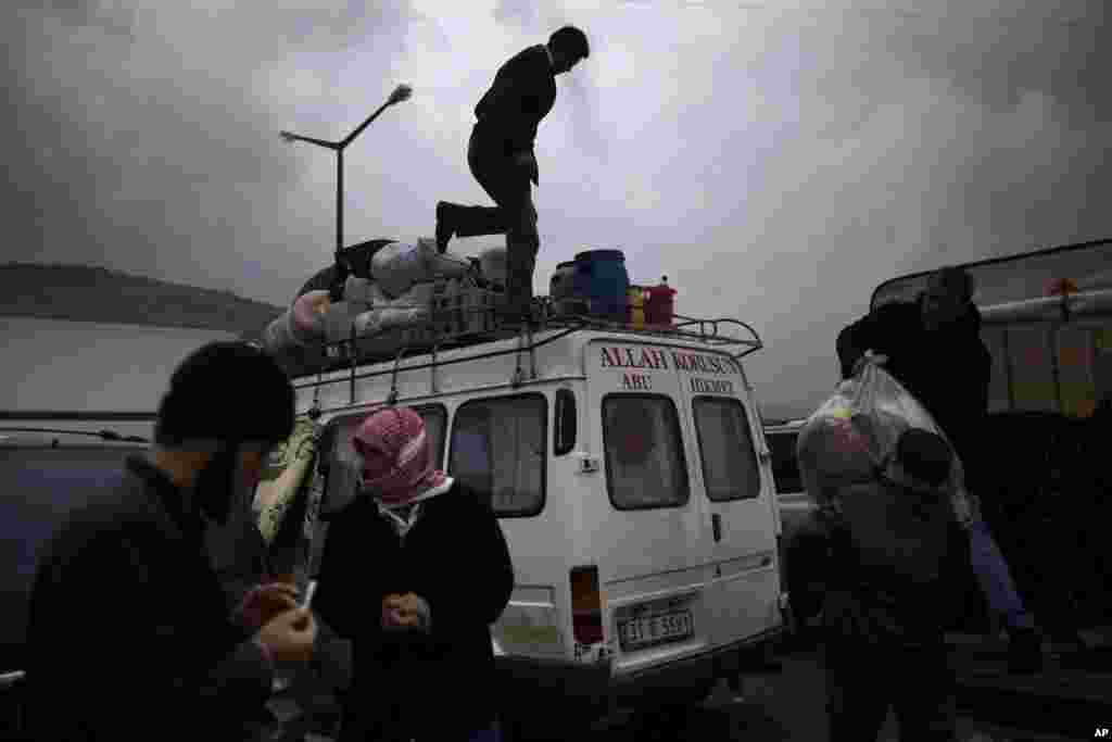 Syrian refugees,who fled their home in Idlib due to a government airstrike, load their belongings into a vehicle after crossing into Cilvegozu, Turkey, December 20, 2012.