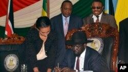 Le président Salva Kiir du Soudan du Sud signe l'accord de paix avec à l'arrière-plan à gauche le président du Kenya Uhuru Kenyatta et à droite le Premier ministre éthiopien Hailemariam Desalegn mercredi 27 aout 2015 à Juba, Soudan du Sud.