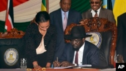 President Sudan Selatan Salva Kiir (duduk) menandatangani perjanjian damai dengan pemberontak di ibukota Juba, hari Rabu (26/8).