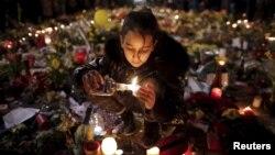یک دحتر برای قربانیان حملات بروکسل شمع روشن می کند