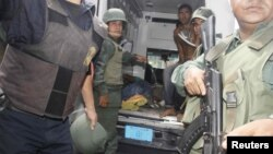 Militares venezolanos evacuan a heridos durante la requisa en el centro penitenciaría de Uribana.