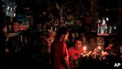 Seorang penjaga toko melayani pembeli saat pemadaman listrik di Dhaka, Bangladesh, 1 November 2014.