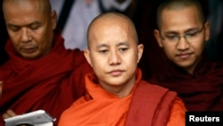 FILE - Buddhist monk Wirathu (C), leader of the 969 movement, greets other monks as he attends a meeting on the National Protection Law at a monastery outside Yangon.