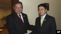 Indonesian President Susilo Bambang Yudhoyono, left, shakes hands with Thai Prime Minister Abhisit Vejjajiva before their trilateral meeting with Cambodia in Jakarta, Indonesia, May 8, 2011.