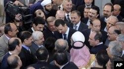 Bức ảnh Tổng thống Syria al-Assad (giữa) bắt tay những người dự lễ tại một đền thờ Hồi giáo vào ngày đầu tiên lễ Eid al-Adha, 26/10/12, do thông tấn xã SANA của Syria công bố