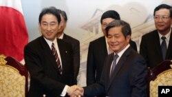 Menlu Jepang Fumio Kishida, kiri, berjabat tangan dengan Menteri Perencanaan dan Investasi Vietnam Bui Quang Vinh.