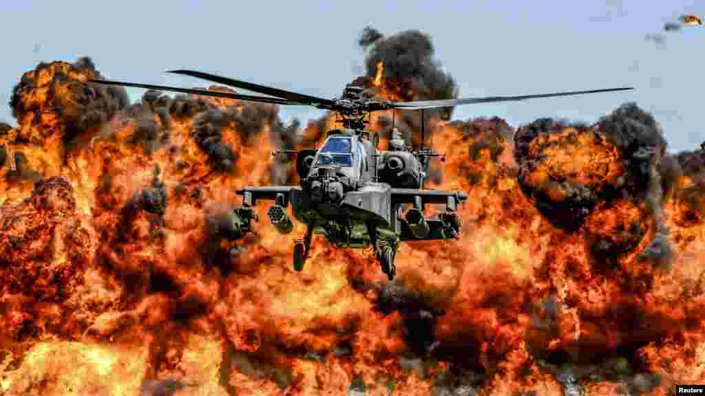 ឧទ្ធម្ភាគចក្រ AH-64D Apache ហោះចំពីមុខអណ្តាតភ្លើងដ៏សន្ធោសន្ធៅក្នុងកម្មវិធីតាំងបង្ហាញមួយរបស់ឆ្មាំអាកាសជាតិនៃភាគខាងត្បូងរដ្ឋកាលីហ្វ័រញ៉ានៅបន្ទាយ McEntire Joint National Guard។