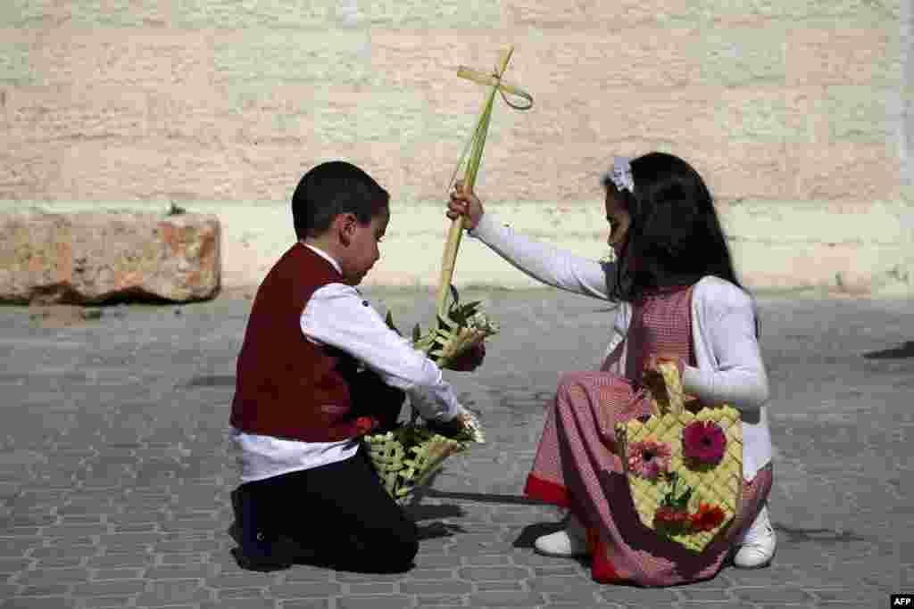 ក្មេងប្រុស និងក្មេងស្រីប៉ាឡេស្ទីនកាន់ឈើឆ្កាងមួយ នៅពេលពួកគេចូលរួមទិវា Easter នៅព្រះវិហារ Church of Saint Porphyrius នៅក្នុងក្រុង Gaza។