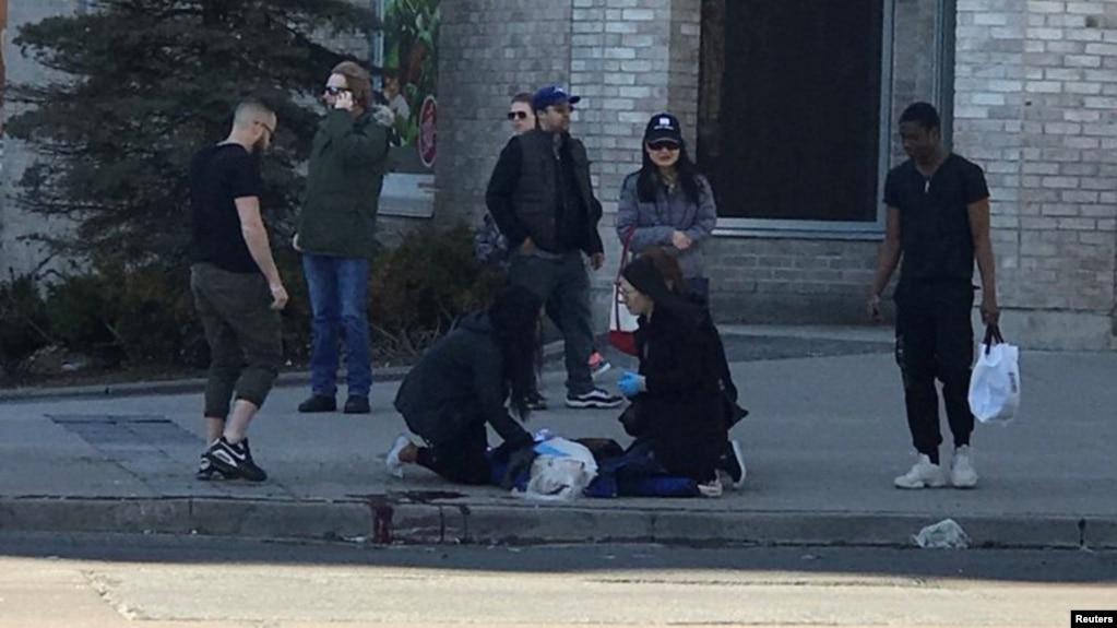Прохожие помогают пострадавшему от удара минигрузовика человеку. Торонто, Канада. 23 апреля 2018 г.