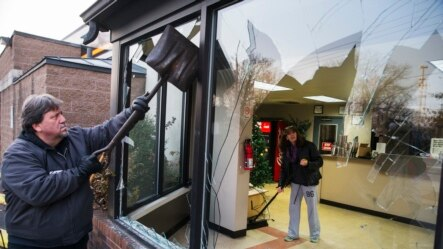 2014年11月26日,密苏里州弗格森的一家店主夫妇一起清除昨天晚上抗议者留下的涂污。