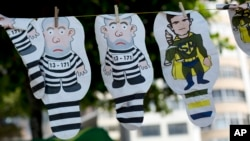 FILE - A set of inflatable dolls in the likeness of former President Luis Inacio Lula da Silva in prison garb and Judge Sergio Moro as a superhero hang on a line for sale during a protest against corruption and in support of the Car Wash investigation on Copacabana beach, in Rio de Janeiro, Brazil.
