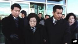 12月26号,韩国前总统金大中的遗孀李姬镐(中)和吊唁团中的其他成员抵达北韩