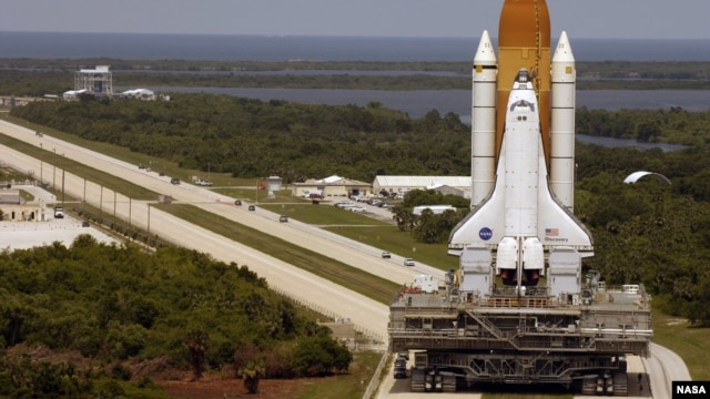 FILE - Space Shuttle Discovery, resting on the Mobile Launcher Platform, turns the corner on the crawlerway as it rolls back from Launch Pad 39B to the Vehicle Assembly Building, March 26, 2005. (Image Credit: NASA/KSC)