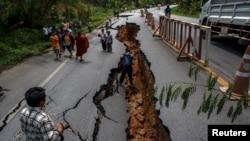 Cư dân đi bộ trên con đường cao tốc bị hư hại sau trận động đất ở Chiang Rai, miền bắc Thái Lan, ngày 6/5/2014.