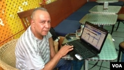Mohamed Suleyman in New York City monitors a live social media newsfeed from his native Cairo. (VOA Photo A. Phillips)
