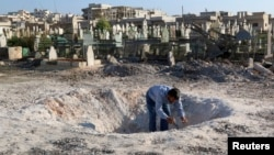 A man inspects a hole in the ground after what activists said was an airstrike by forces loyal to Syria's President Bashar al-Assad in Khan Sheikhoun, northern Idlib province, Dec. 26, 2014.