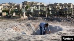 Seorang warga memeriksa lubang bekas serangan udara pasukan Suriah di provinsi Idlib (foto: dok).