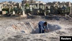 一名男子撿視在忠於阿薩德部隊空襲伊德利卜後在地面上造成一個大洞。