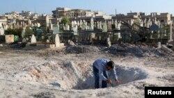 26일 시리아 정부군의 공습으로 생긴 것으로 추정되는 구덩이를 한 남성이 살펴보고 있다.