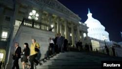 Para anggota DPR AS meninggalkan Gedung Capitol setelah melakukan pemungutan suara larut malam untuk RUU fiskal (16/10). (Reuters/Jonathan Erns)