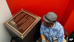 Martin L. Mathews, co-founder of St. Louis' Mathews-Dickey Boys' & Girls' Club, pauses to read a plaque in memory of Michael Brown during the dedication of a new community empowerment center, July 26, 2017, in Ferguson, Mo.