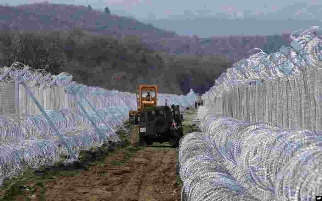 Veículos do exército da Macedónia deslocam-se entre dois muros de arame farpado na fronteira sul com a Grécia.
