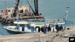 Petugas kepolisian menginspeksi kapal yang ditarik ke pelabuhan Catania, selatan Italia (10/8). Kapal ini dilaporkan mengangkut sedikitnya 100 imigran sebelum kandas di lepas pantai Italia.
