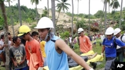 Rescuers carry a body retrieved from a landslide caused by an earthquake in La Libertad, Negros Oriental in central Philippines February 7, 2012.