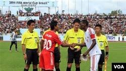 Kapten Birma Khin Maung Lwin (kiri) berjabat tangan dengan Bait Doorbeen Fawzi Bashir Rajab dari Oman sebelum pertandingan leg kedua kualifikasi Piala Dunia 2014 di stadion Thuwuna, Kamis (28/7). Pertandingan itu akhirnya dihentikan karena para pendukung