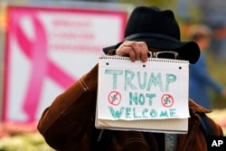 A man holds a sign outside the University of Pittsburgh's Presbyterian Hospital before the arrival of President Donald Trump's motorcade in Pittsburgh, Oct. 30, 2018.