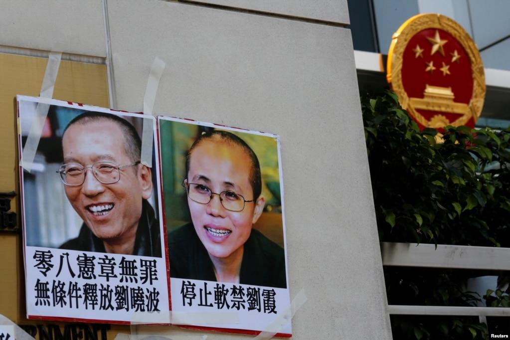2017年6月27日,一些人在香港中联办外面示威,举着刘晓波夫妇的照片。