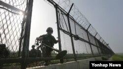 지난 12일 한국 경기도 파주시 한강하류에서 육군 9사단 장병이 지뢰탐지기를 들고 철책 통문을 나서고 있다.