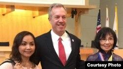 Cô Đỗ Minh Ngọc với dây đeo có cờ vàng chụp hình chung với Đại sứ Ted Osius sau buổi thảo luận (ảnh Bùi Văn Phú).