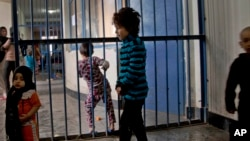 FILE - Children walking through the prison in Badam Bagh, Afghanistan's central women's prison, in Kabul.