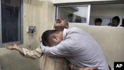 星期二在巴基斯坦的奎達市的一所醫院親屬悼念他們在一場大火中喪生的親人