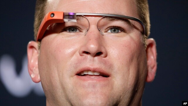 FILE - Stanford offensive coordinator Mike Bloomgren, wearing Google Glass, answers questions from the media during a news conference, in Los Angeles.