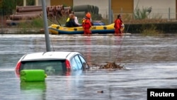 Rescue workers pulling a boat along, wade on a flooded street at San Gavino Monreale in Sardina island Nov. 18, 2013.