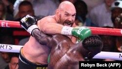 ၿဗိတိန္ႏိုင္ငံသား ဟဲဗီးဝိတ္ခ်န္ပီယံေဟာင္း Tyson Fury (ဘယ္) က အေမရိကန္ လက္ေဝွ႔အေက်ာ္အေမာ္ Deontay Wilder (ညာ) ကို အလဲထိုးေနစဥ္။ (Photo - AFP )