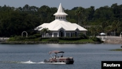 A search boat passes Disney's Fairy Tale Weddings Chapel in the Seven Seas Lagoon, located near the Grand Floridian, as police hunted for signs of a 2-year-old boy who was dragged by an alligator into the lagoon at the Walt Disney World resort in Orlando, Florida, U.S., June 15, 2016. REUTERS/Adrees Latif
