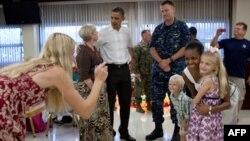 Барак и Мишель Обама вместе с семьями американских морских пехотинцев на Гавайах. 25 декабря 2010г.