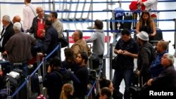 FILE - Passengers with their baggage move through the Tom Bradley International Terminal at Los Angeles International Airport (LAX), California. Police say no gunman has been found and no shots were fired.