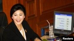 Perdana Menteri Thailand Yingluck Shinawatra tersenyum di tengah proses pemungutan suara untuk mosi tidak percaya di Bangkok (28/11).