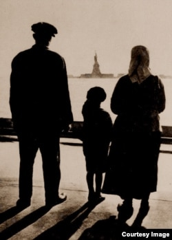 An immigrant family views the Statue of Liberty from Ellis Island